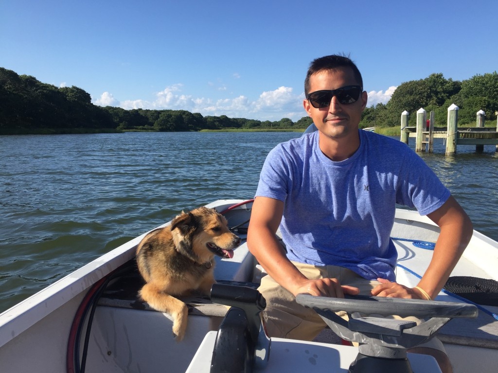 Adam, looking chill af in a boat with his awesome dog, Rory